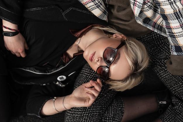 Giovane donna bionda abbastanza attraente in occhiali da sole alla moda in vestiti di moda neri della gioventù che riposano sulla ragazza. le ragazze sorelle alla moda e moderne si rilassano sulla strada per strada
