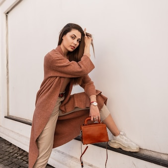Giovane donna abbastanza attraente nella moda bellissimo cappotto elegante in pantaloni beige in scarpe da ginnastica alla moda con borsa in pelle in posa vicino al muro in città. la ragazza alla moda sveglia raddrizza i capelli. dolce signora