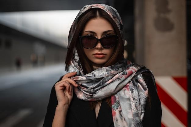 Modello di moda giovane donna abbastanza attraente in elegante scialle alla moda in occhiali da sole in cappotto nero in posa in città per strada. ragazza alla moda di affari all'aperto il giorno di primavera. signora moderna di bellezza.