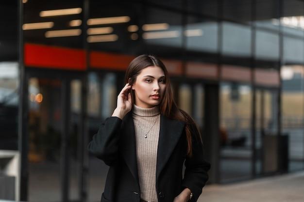 Modello di moda giovane donna abbastanza attraente raddrizza i capelli all'aperto in una giornata di primavera. bella ragazza carina in un elegante cappotto nero posa vicino a un edificio moderno di vetro in città. signora elegante.