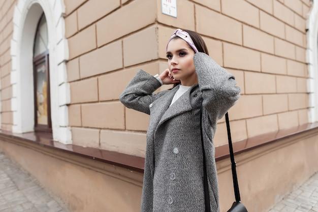 Giovane donna abbastanza attraente in bandana glamour in bel cappotto grigio con borsa in posa vicino a edificio d'epoca in città. il modello di splendida ragazza carina cammina per strada. abbigliamento da donna per la moda primaverile giovanile.