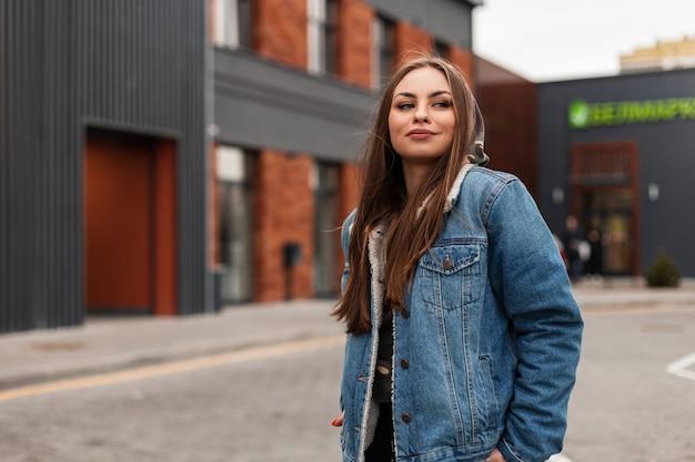 Piuttosto attraente giovane donna in cappuccio in elegante giacca di jeans blu si trova sulla strada vicino a un edificio d'epoca. modello di moda americano alla moda ragazza carina all'aperto. stile giovanile casual.
