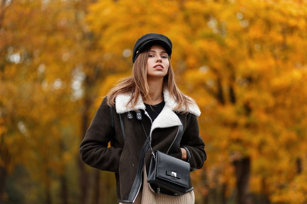 Giovane donna abbastanza bella in una giacca elegante marrone in un cappello elegante con una visiera con una borsa alla moda in pelle in posa nel parco. modello di moda ragazza moderna in abiti autunnali alla moda all'aperto.