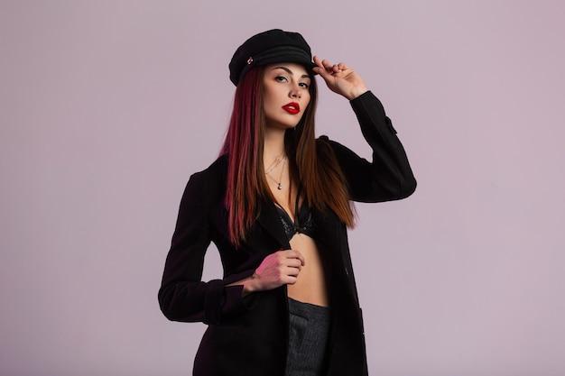 Modello di moda abbastanza bella giovane donna con labbra rosse con capelli lunghi in cappotto nero alla moda raddrizza berretto elegante vicino alla parete rosa in studio. ragazza bruna di lusso in abiti classici al chiuso.