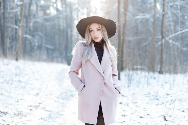 La giovane donna abbastanza bella in vestiti glamour caldi alla moda sta camminando in un cappello elegante in un bosco innevato in una giornata di sole invernale. ragazza moderna attraente alla moda.