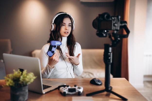 Una bella blogger sorpresa in cuffia è in streaming in diretta parlando di videogiochi. influencer giovane donna live streaming tenere il joystick.