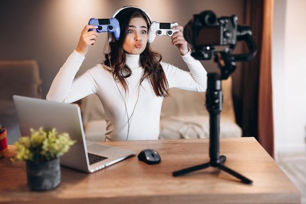 Bella blogger donna in cuffia è in streaming live parlando di videogiochi. influencer giovane donna si diverte in live streaming.