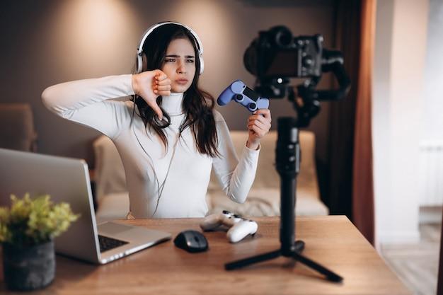 Bella blogger donna in cuffia è in streaming live parlando di videogiochi. influencer giovane donna in diretta streaming. non mi piace.
