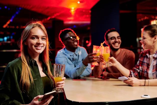Bella ragazza bionda con un bicchiere di succo d'arancia e telefono cellulare seduti a tavola con i suoi amici che tostano