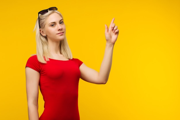 Bagnino abbastanza biondo in costume da bagno rosso e occhiali da sole punta il dito su sfondo giallo