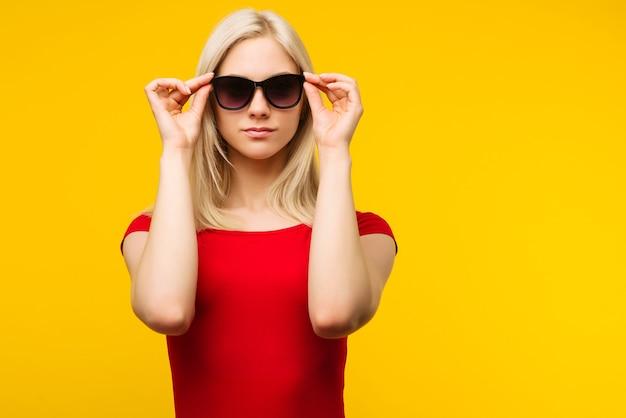 Bagnino abbastanza biondo in costume da bagno rosso e occhiali da sole su giallo