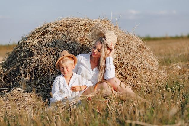 Donna dai capelli lunghi abbastanza bionda con figlio piccolo biondo al tramonto rilassante nel campo e assaporando la frutta da un cestino di paglia. estate, agricoltura, natura e aria fresca in campagna.