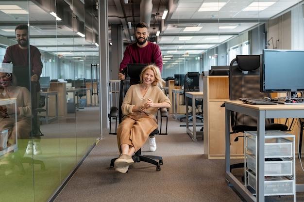 Donna di affari matura abbastanza bionda che si diverte mentre è seduto in poltrona e il suo collega più giovane spingendolo lungo il corridoio dell'ufficio moderno
