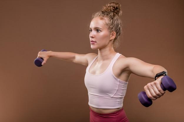 Bella bionda sportiva in abbigliamento sportivo mantenendo le braccia tese durante l'esercizio fisico con manubri per i muscoli in isolamento