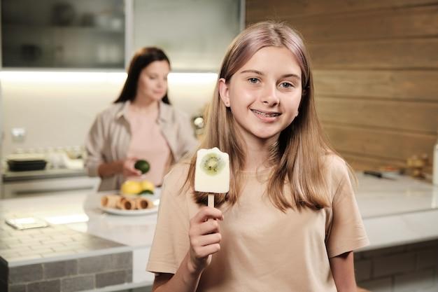 Bella bionda ragazza adolescente che ti mostra gelato eschimese fatto in casa con fetta di kiwi fresco mentre lo mangi davanti alla telecamera in cucina