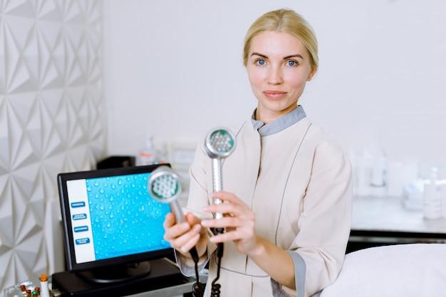 Cosmetolotgista ed estetista medico donna bionda graziosa in possesso di uno strumento per la terapia della fototerapia con fototerapia a led fototerapia fototerapia