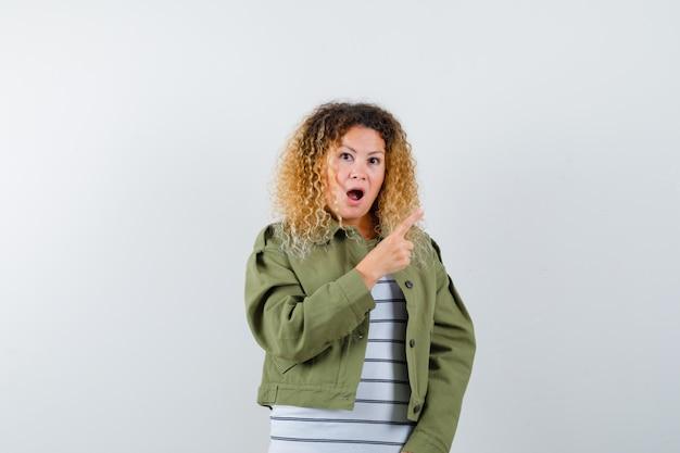 Donna abbastanza bionda in giacca verde che punta all'angolo in alto a destra e guardando sorpreso, vista frontale.
