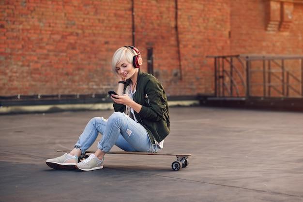 Musica d'ascolto della donna abbastanza bionda in cuffie rosse e nel telefono usando mentre sedendosi sul longboard al muro di mattoni.