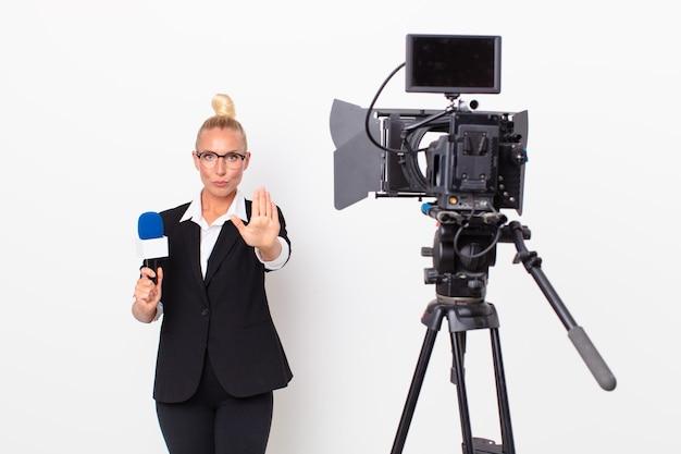 Bella donna bionda che sembra seria mostrando il palmo aperto che fa il gesto di arresto e tiene in mano un microfono. concetto di presentatore