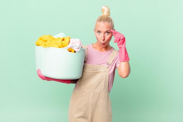 Bella donna bionda che sembra sorpresa, realizzando un nuovo pensiero, idea o concetto che lava i vestiti concept