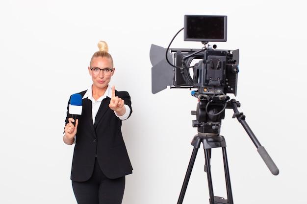 Donna abbastanza bionda che sorride con orgoglio e sicurezza facendo il numero uno e tenendo in mano un microfono. concetto di presentatore