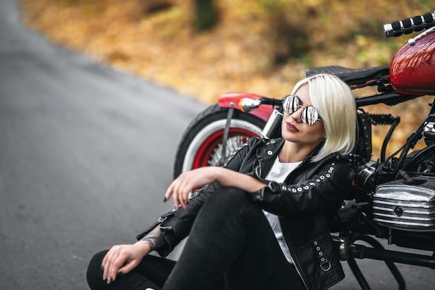 Ragazza abbastanza bionda del motociclista in occhiali da sole che si siede vicino al motociclo rosso sulla strada nella foresta