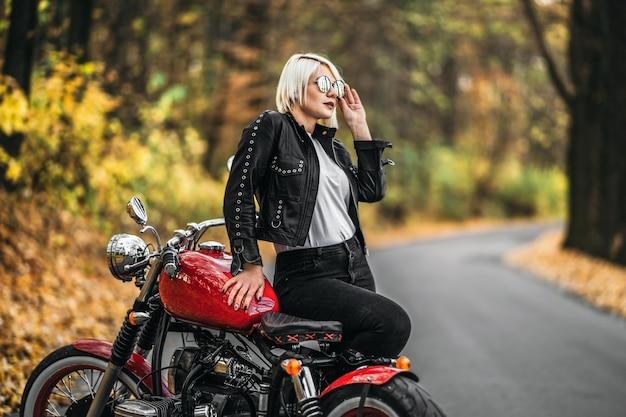 Ragazza abbastanza bionda motociclista in occhiali da sole con motocicletta rossa sulla strada nella foresta