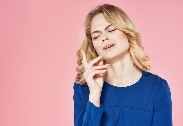 Bella bionda in abito blu che tiene in mano lo sfondo rosa dello studio dei capelli