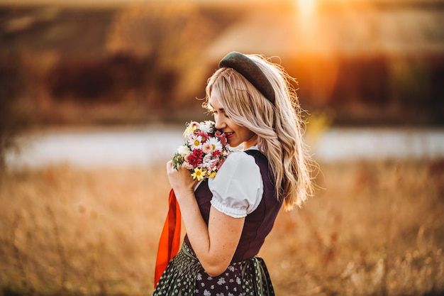 Bella ragazza bionda in dirndl, in piedi all'aperto nel campo, con in mano un mazzo di fiori di campo.