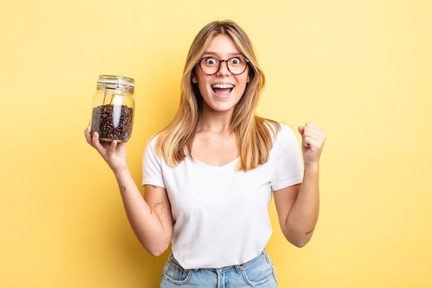 Bella ragazza bionda che si sente scioccata, ride e celebra il successo. concetto di chicchi di caffè