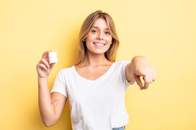 Bella ragazza bionda che punta alla telecamera scegliendo te. concetto di bottiglia di pillole