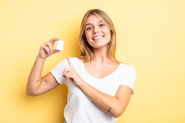 Bella ragazza bionda che sorride allegramente, si sente felice e indica il lato. concetto di bottiglia di pillole