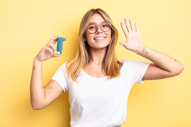 Bella ragazza bionda che sorride felicemente, agitando la mano, dandoti il benvenuto e salutandoti. concetto di inalatore per l'asma