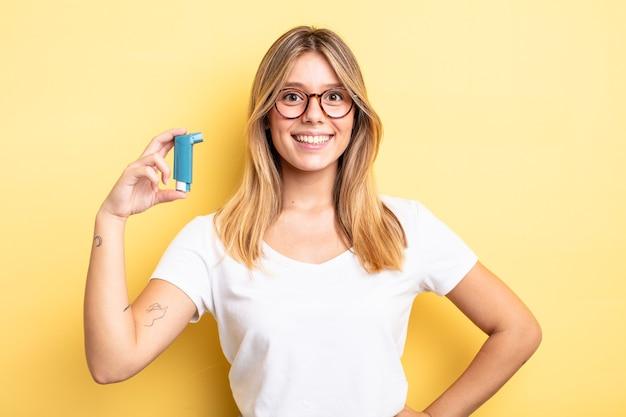 Bella ragazza bionda che sorride felicemente con una mano sull'anca e sicura di sé. concetto di inalatore per l'asma