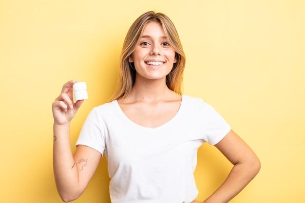 Bella ragazza bionda che sorride felicemente con una mano sull'anca e sicura di sé. concetto di bottiglia di pillole