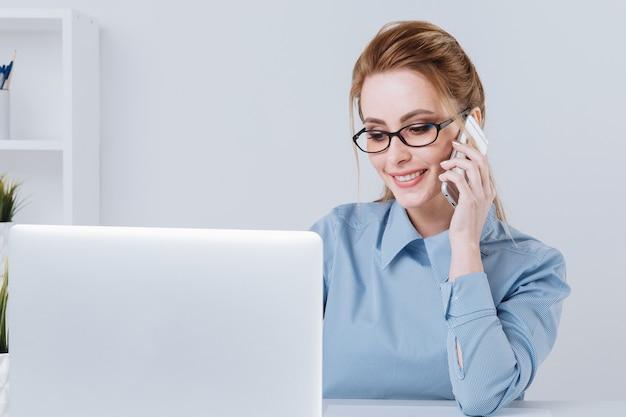 Telefono di conversazione della ragazza di ufficio abbastanza bionda al suo posto di lavoro.