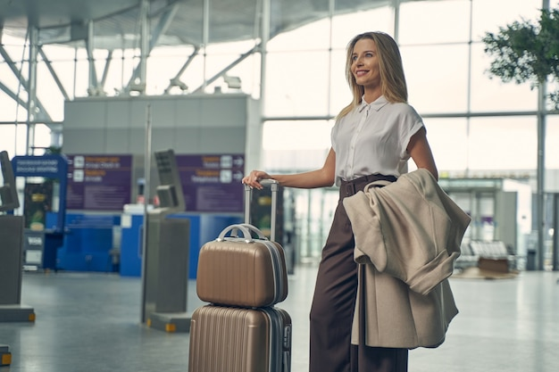 Bella donna bionda che mostra il suo sorriso mentre sta per fare un viaggio d'affari