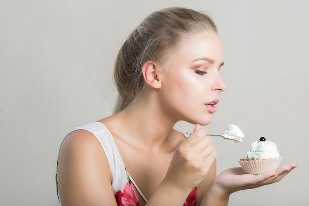 Bella donna bionda che mangia un gustoso dessert dolce con crema al burro