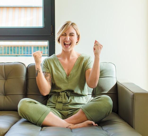 Donna abbastanza bionda che si sente felice, positiva e di successo, che celebra la vittoria, i risultati o la buona fortuna