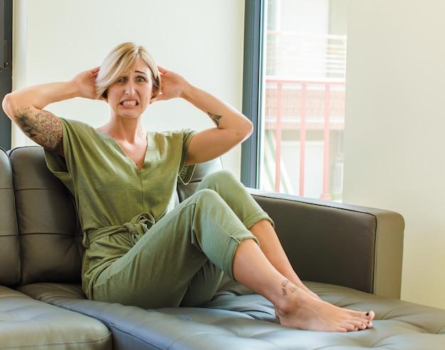 Donna abbastanza bionda che si sente stressata, preoccupata, ansiosa o spaventata, con le mani sulla testa, in preda al panico per errore