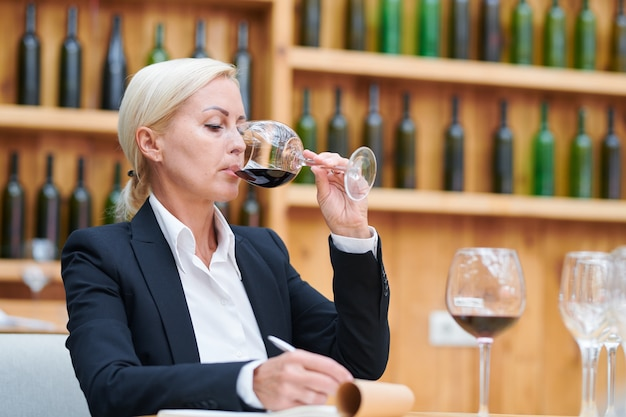 Bella donna bionda in abiti da cerimonia che prende appunti sulla qualità e il sapore del vino rosso mentre lo assaggia