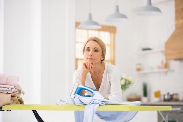 Bella donna bionda in piedi vicino al tavolo da stiro e guardando pensieroso