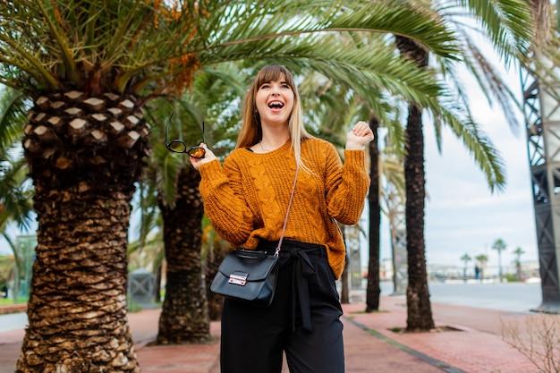 Bella donna bionda che viaggia e si gode l'autunno a barcellona,