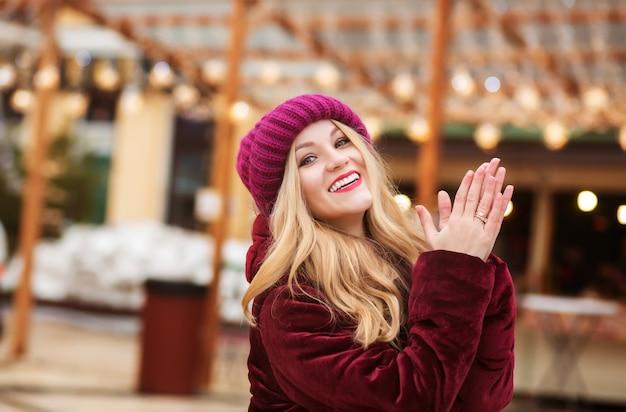Bella donna bionda che indossa abiti invernali caldi, in posa sullo sfondo delle luci