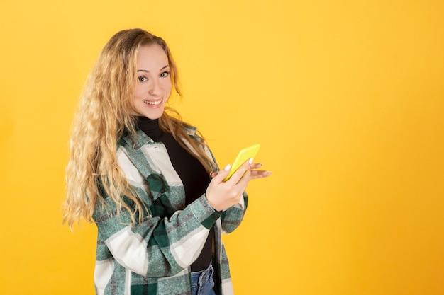 Bella donna bionda con abiti casual, con il suo telefono cellulare sorridente guardando la fotocamera, sfondo giallo