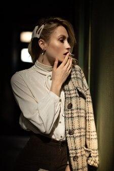 Bella ragazza bionda in elegante camicetta bianca e giacca di tweed a scacchi tocca sensibilmente le labbra e guarda a destra nel corridoio buio