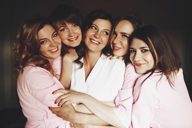 La bella sposa e le ridenti damigelle in abiti rosa abbracciano ogni altra tenera come le sorelle