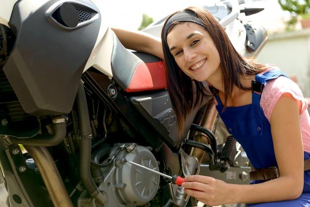 Ragazza graziosa del brunette nella meccanica della motocicletta