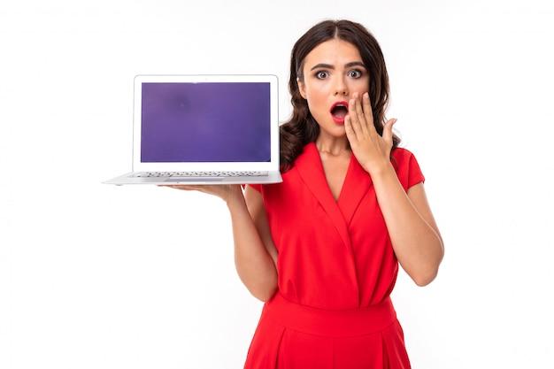 Ragazza graziosa del brunette in vestito rosso che tiene un computer portatile con il modello in sue mani su bianco