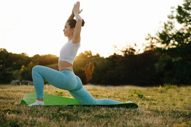 Bella ragazza bruna che si rilassa nella natura e pratica lo yoga sotto i raggi del sole. spazio per il testo